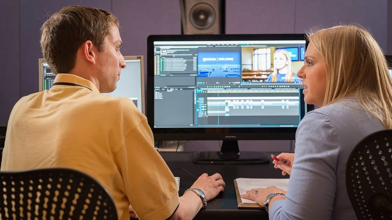A man and woman working together on video editing software